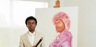 Young artist poses in front of a painting of an older woman