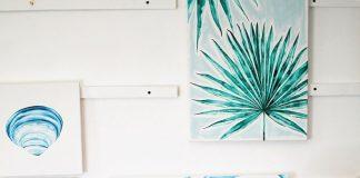 Artist Laurie Duncan paints a blue design on a canvas