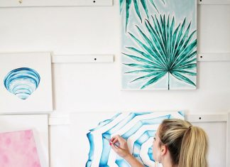 Artist Laurie Duncan paints a blue design on a canvas