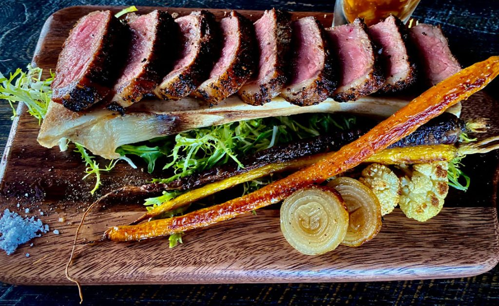 Grilled Flat Iron steak, roasted bone marrow, root vegetables, Riviera house steak sauce at Riviera by Fabio Viviani